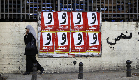 A woman walks past campaign posters for the Arab-led Hadash Party in the Israeli-Arab city of Umm al-Fahm, Dec. 26, 2012.